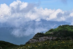 Cloud envelops rocky mountains and alpine meadows. Beautiful landscape of National Park of Russia. Forest and mountains in fog in cloudy weather.