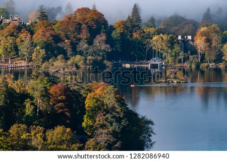 Cloud over Derwent Water lake in the Lake District Cumbria with Autumn colours and view of boathouse in the clear water. #1282086940