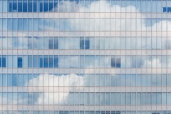 Cloud reflected in windows of modern office building