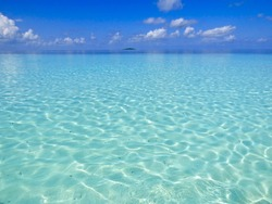 Cloud reflections on the water surface of the Indian Ocean on a sunny day on the Maldives.