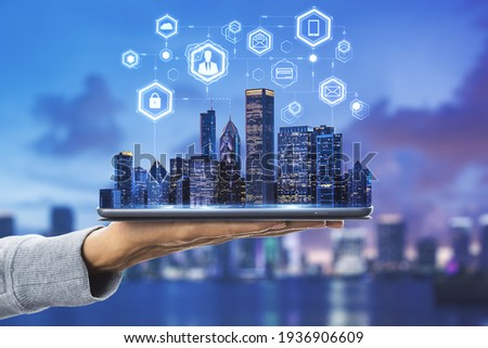 Cloud technology in smart city concept with human hand carries digital tablet with megapolis city skyscrapers and digital social network symbols above at blurry skyline background