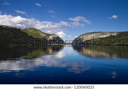 Clouded blue sky reflected in the calm Tagus river lake at Portas de Rodao, Portugal.