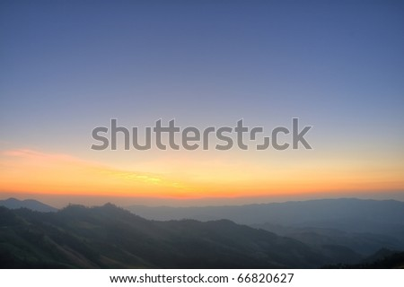 clouded orange sky with mountain