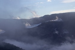 clouds and mist in the valley in the High Atlas mountains with a clear blue sky