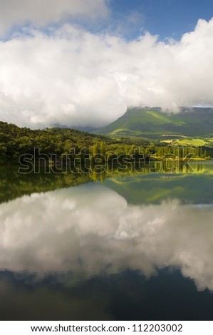 Clouds and mountains reflection in the Marono reservoir