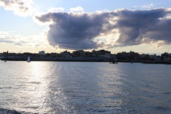 clouds and sun over city on ocean edge from low angle with blue water and small waves view from water with blue and gray clouds and blue sky harbor with buildings along shore