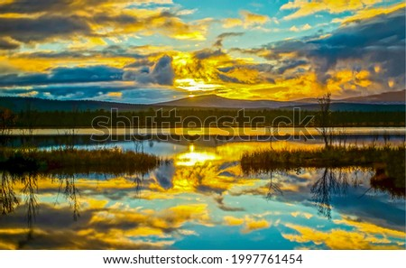 Clouds are reflected in the lake at dawn. Early morning on mountain lake. Lake in early morning. Lake at dawn