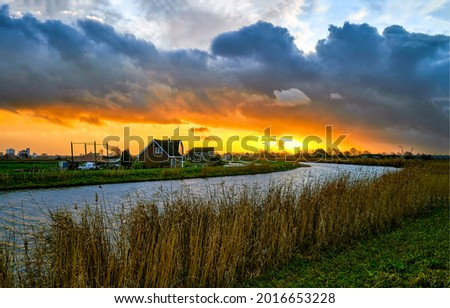 Clouds at sunset over the river in the village. Sunset river village. River village at sunset landscape