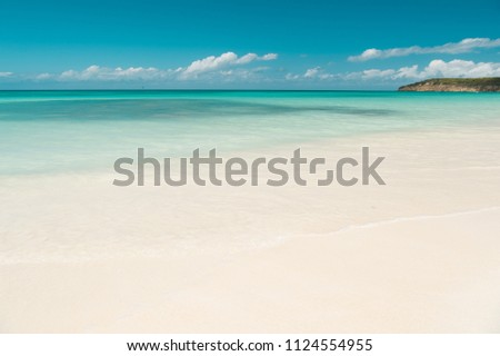Clouds blue sky over calm sea beach tropical island. Tropical paradise beach with sand. Travel experts reveal Antigua best beaches. Sand pearlescent white claim as fine as powder. Paradise island.