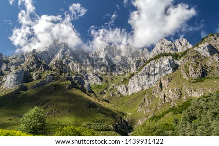 Clouds cling to the peaks of the highest peaks of the Picos de Europa National Park, Spain, a summer afternoon