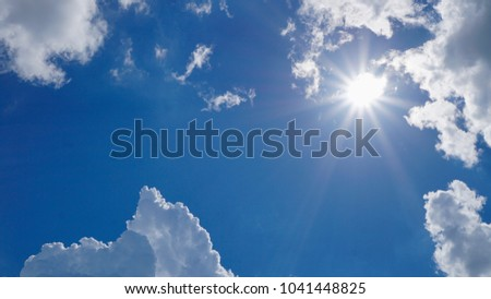 Clouds formations with sun flare over bluesky background. Copy space