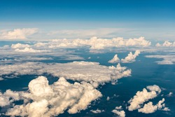 Clouds from a height of ten kilometers. Sea of clouds from the plane window. Blue sky and white clouds. The Heavenly World of White Silence