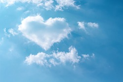 Clouds heart shaped patterns on bright blue sky with mild wind and reflection light from the sun for background