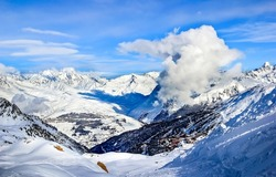 Clouds in snowy mountains landscape. Winter mountain snow panorama. Snowy mountain landscape