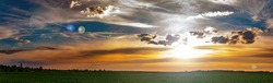 Clouds in the orange rays of the sunset over a green farm field. Sunny sunset. Blue sky with clouds. Cloudy horizon. Evening twilight. Agriculture. Farm field. Morning sunrise. Natural landscape.