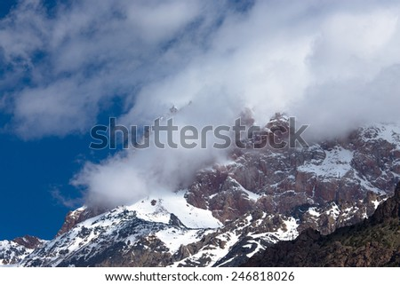 Clouds lie on the snow-covered tops of the rocks. Landscape.