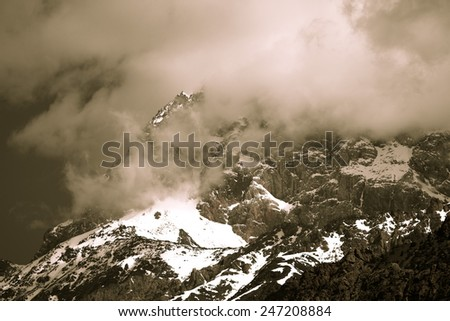 Clouds lie on the snow-covered tops of the rocks. Landscape. Toned.