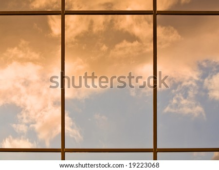 Clouds lit by the setting sun reflecting in a modern office building windows