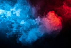 Clouds of isolated colored smoke: blue, red, orange, pink; scrolling on a black background in the dark close up.
