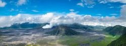 Clouds of smoke coming from crater of Mount Bromo and drifting by, Tengger Semeru national park, East Java, Indonesia. Landscape with erupting volcano in sunny day. Eruption and volcanic activity.
