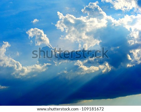 Clouds on sky with sunbeams. Summer time.