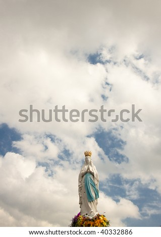 Clouds on the sky and Big figure of the Madonna in Lourdes - France.