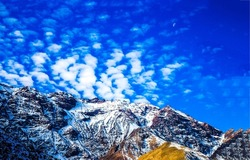 Clouds over a mountain peak covered with snow. Mountain peak snow. Mountain sky clouds