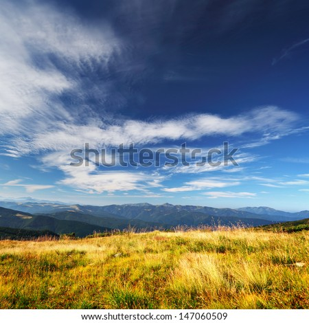 clouds over mountains and yellow grass on foreground, square panorama in summer day