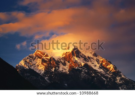 Clouds over the mountain peak at dusk