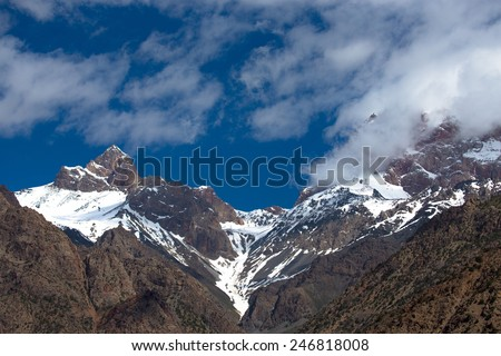 Clouds over the snow-covered tops of the rocks. Landscape.