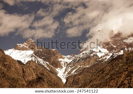 Clouds over the snow-covered tops of the rocks. Landscape. Toned.
