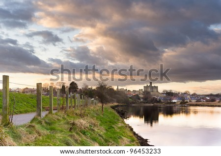 Clouds over Warkworth Castle / Atmospheric sky reflecting Warkworth Castle in the river Coquet