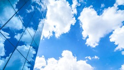 clouds reflected in the many mirrored facets of a modern office building