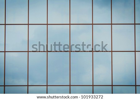 Clouds reflected in windows of modern office building symmetric background