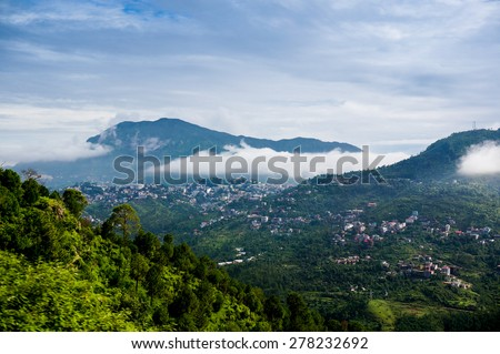 Clouds rolling between the hills of himachal pradesh in India. The small hill villages are visible among the green hills