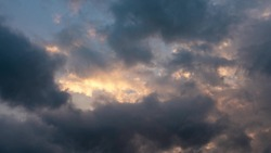 CLOUDS SHOWS THE IMPACT OF GLOBAL CLIMATE WARMING. Abstract clouds backgrounds. Dark dramatic clouds move fast. Ragged thunderclouds cover the sunny areas of the sunset sky.