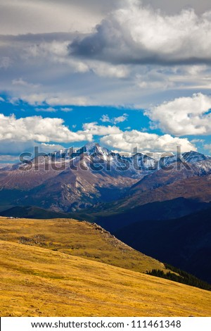 Clouds swoop by and over 14,259 feet high Longs Peak on a gorgeous autumn day in Rocky Mountain National Park, Colorado along Trail Ridge Road