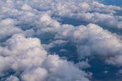 Clouds view from the sky with visible part of land below