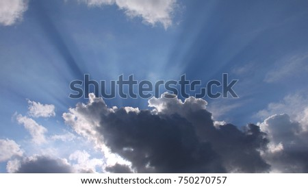 Shutterstock Clouds with Crepuscular Rays and Blue Sky - Photograph of clouds with a setting sun causing crepuscular rays to shine upwards from the clouds, into a bright blue sky.
