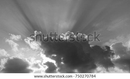 Shutterstock Clouds with Crepuscular Rays - Black and white photograph of clouds with a setting sun causing crepuscular rays to shine upwards from the clouds.