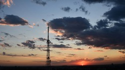Cloudscape with industrial communication tower and dark purple clouds while golden sunbeams shining through. Red orange cloudscape of sunset. Dark dramatic sky sundown