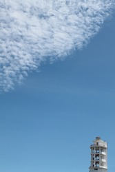 Cloudy blue sky and Manado city lighthouse on right corner. Diagonal composition