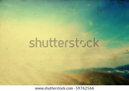 Cloudy blue sky upon green mountain ridge with added grunge retro effect texture
