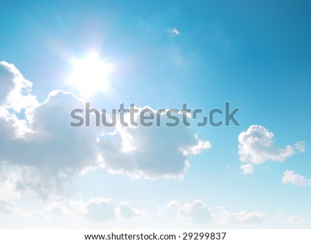 Cloudy blue sky with sun and lens flair