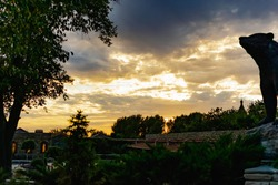 Cloudy evening sky over a residential area, over a wooden fence. Overcast gray clouds over a yellow sunset, through trees and blue dark saturated sky