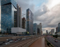 Cloudy gloomy Tel Aviv city before the sunset. Modern glass skyscrapers and automobile Ayalon highway