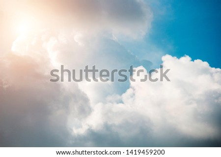 Cloudy in the bright blue sky with the sun light that passes through the clouds for background or graphic design