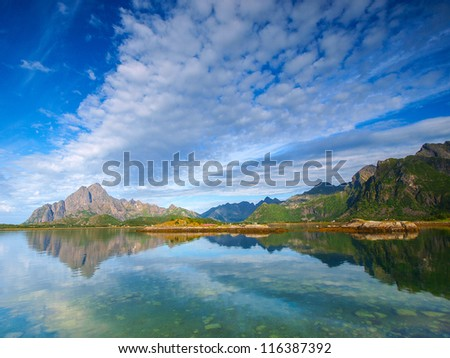 Cloudy morning in norwegian fiord reflection in water