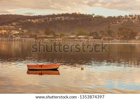 Cloudy morning over Boggy Creek.Lone boat in foreground.  Merimbula  Far South Coast of N.S.W. Australia.