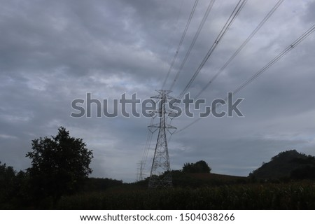 Cloudy sky above High voltage electricity towers with electricity transmittion cables crossing over the rice paddies in rural area.